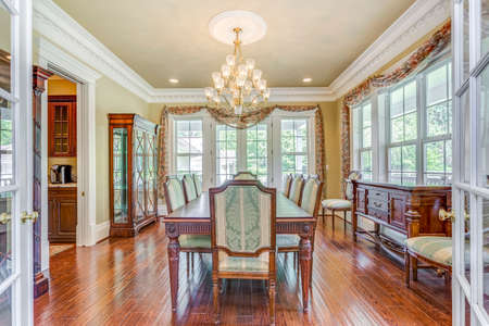 Elegant formal dining room with retro details and big windows. 스톡 콘텐츠