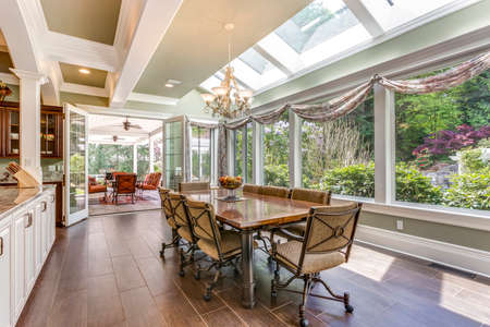 Sun filled dining area with skylight and coffered ceiling. 免版税图像 - 108106292