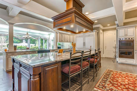 Stunning kitchen room design with large bar style island and coffered ceiling. 免版税图像