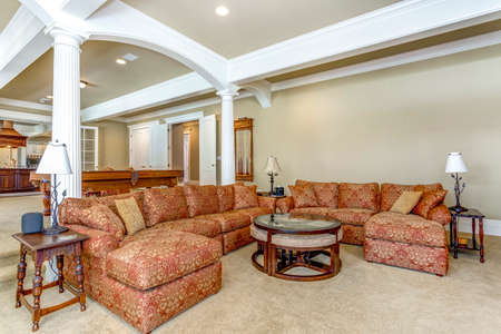 Living room with white columns and large colorful sofa