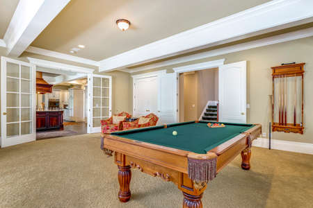 Light brown game room with green billiard table.