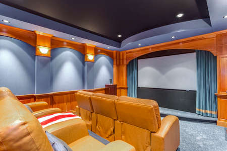 Blue movie room with leather chairs.
