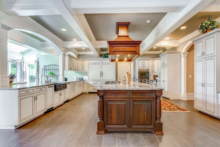 Stunning kitchen room design with large bar style island and coffered ceiling. Foto de archivo