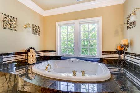 Elegant master bathroom interior boasts tub nook with hot tub and black tile surround.