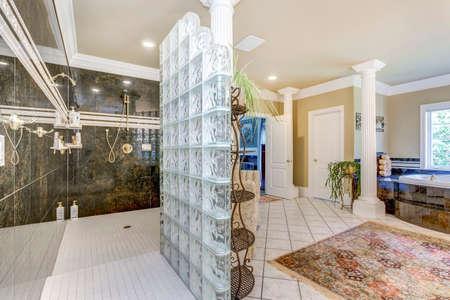 Elegant master bathroom interior with white columns and large walk in shower. Standard-Bild