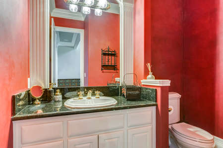 Red bathroom design with white vanity cabinet and marble counter top.