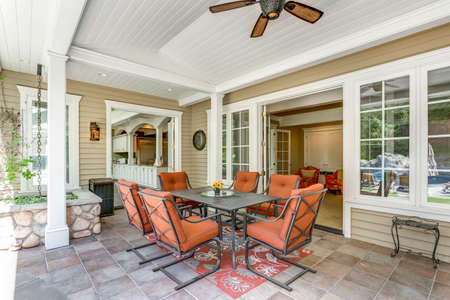 Spacious covered deck area with table and red outdoor chairs under white plank ceiling. Banque d'images - 108106233