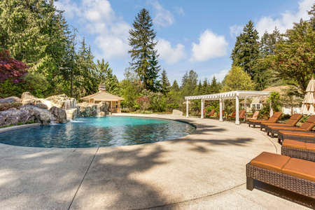 Beautifully landscaped backyard with a large pool, loungers and pergola. Stok Fotoğraf
