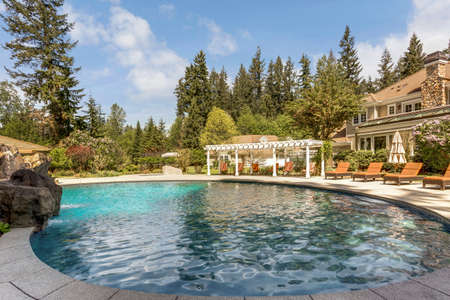 Beautifully landscaped backyard with a large pool, loungers and pergola. Standard-Bild