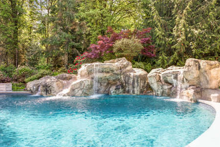 Beautifully landscaped backyard showcases an expansive pool decorated with stone.