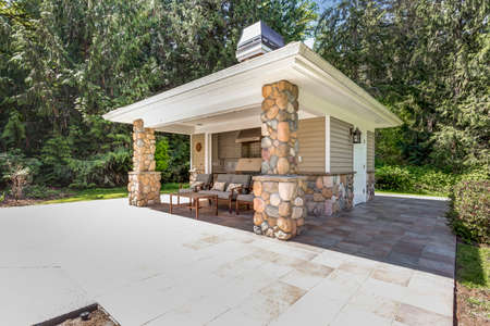 Chic outdoor kitchen space with stone columns and tile flooring.