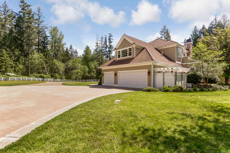 Outstanding country residence with view of a garage, driveway and green grass.