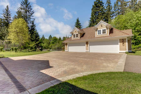 Outstanding country residence with view of a garage, driveway and perfect landscape design.