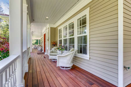 Exterior view of a large country residence with wrap-around deck and cozy sitting area.