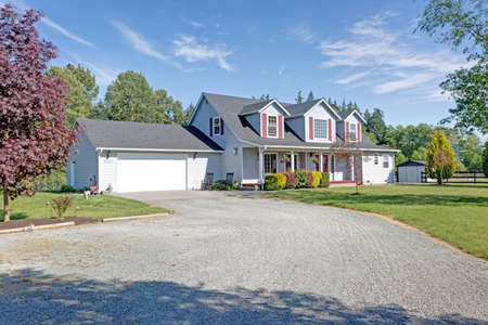 Cute home exterior with red shutters, cozy covered porch and attached garage on a bright summer day. Éditoriale
