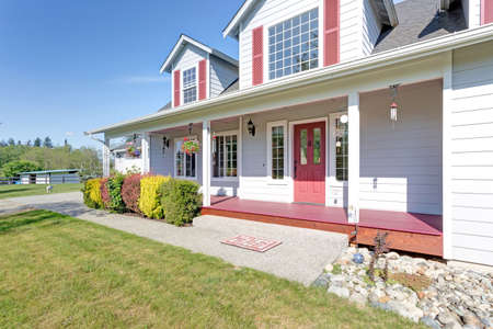 Nice home showcases a cozy covered porch with red front door and well kept lawn in the front yard on a bright summer day.