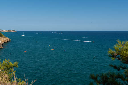 View of the beautiful blue Mediterranean sea with rocks near the shore with waves on a sunny day with boats and sailboats