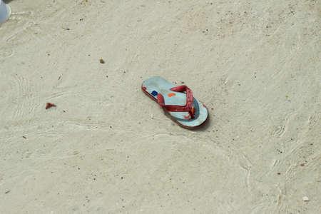 plimsoll: Single shoe on the sand