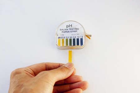 acidity: acidity testing strip against white background Stock Photo