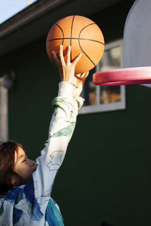 girl slam dunks basketball in backyard photo