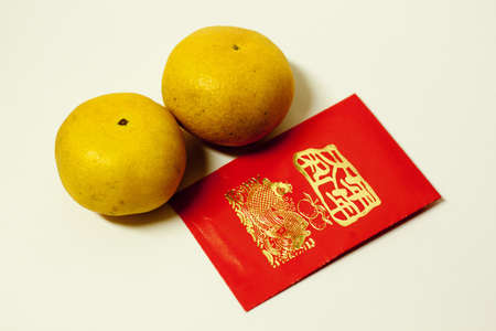 mandarin oranges and lucky red envelope against white background