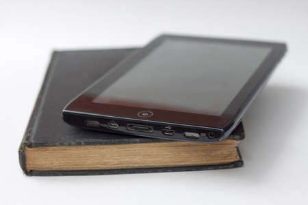 tablet atop book against white background