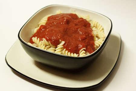 rotini: rotini con salsa de tomate sobre fondo blanco Foto de archivo