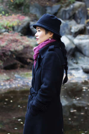overcoat: woman in overcoat by pond - profile