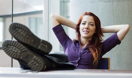 businesswoman smiling, feet up, arms behind her head photo