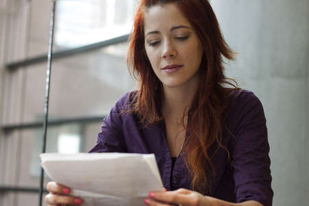 entrepeneur: businesswoman reading over financial documents - smiling