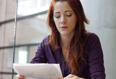 entrepeneur: businesswoman reading over financial documents - speculating