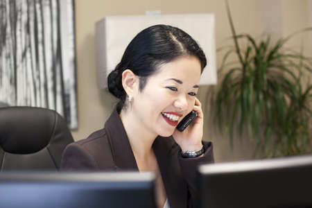 pretty asian businesswoman smiling on phone - computers foreground