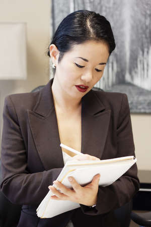 pretty asian businesswoman writing on notebook - standing photo
