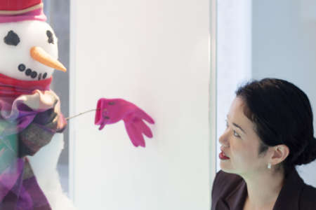 window display: pretty asian lady admiring snowman display in window - wide
