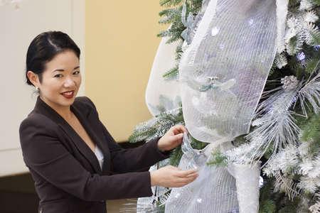 pretty asian lady trimming crhistmas tree - smiling photo
