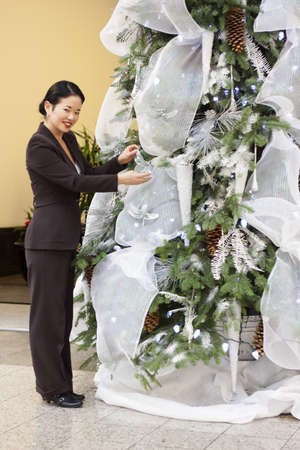 decorating christmas tree: pretty asian decorating christmas tree - standing - smiling