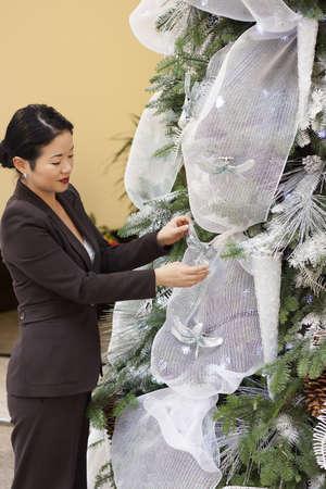 pretty asian lady trimming crhistmas tree photo