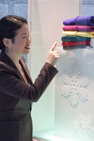 display case: pretty asian lady picking out christmas sweater in display case