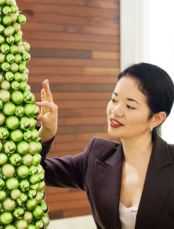 pretty asian lady placing glittery ball on ornate christmas tree - portrait photo