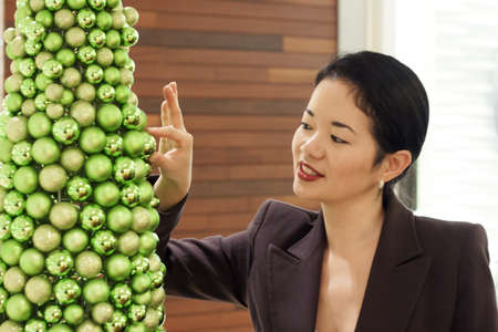pretty asian lady placing glittery ball on ornate christmas tree photo