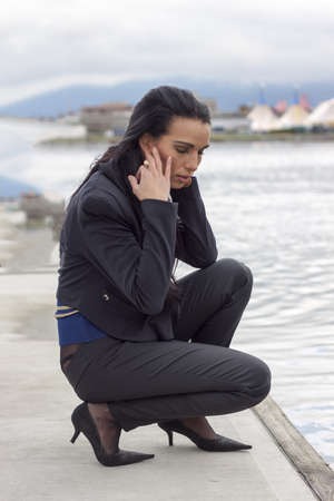 crouched: woman crouched down on pier