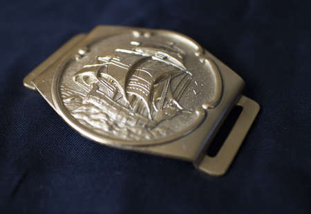 a belt buckle with tall ship carving