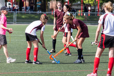 Vancouver, Canada -- June 15, 2013 -- Girls playing field hockey in  Andy Livingstone park in Vancouver, Canada