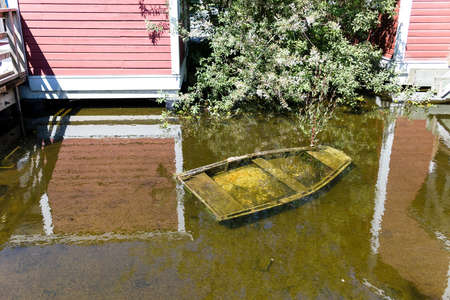 a little submerged rowboat in pond