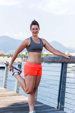 quad: fitness girl quad stretch at seaside rail Stock Photo