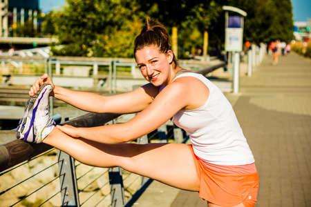 fitness girl quad stretch on rail - tight shot