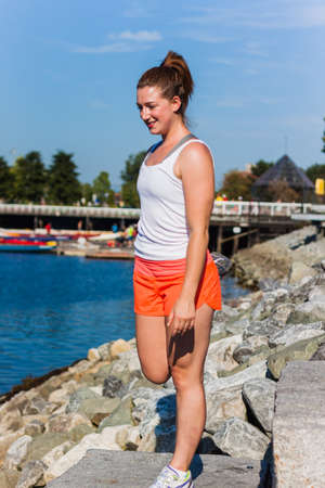 fitness girl stretching on the rocks Stock Photo