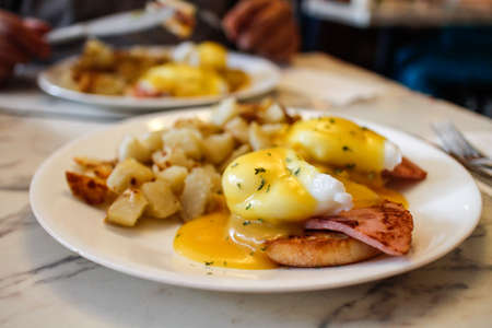 sommige glinsterende Eggs Benedict met opgebakken aardappels Stockfoto