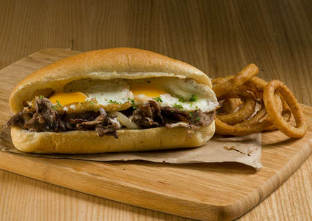 a steak and eggs sandwich with onion rings