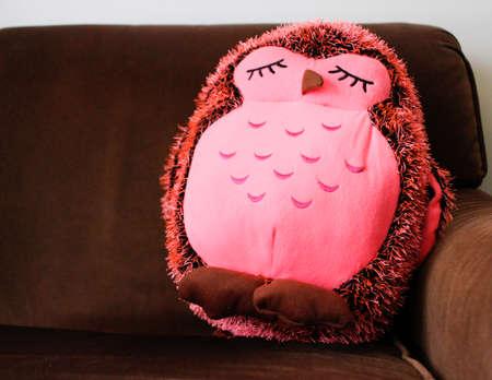 브라운 소파에 귀여운 핑크 박제 올빼미 스톡 콘텐츠